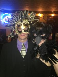 Paul and Eva wearing masks at a Masquerade Ball.
