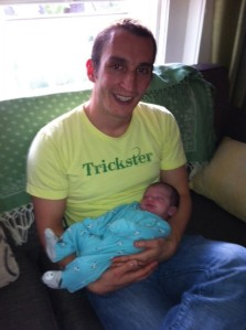 Paul holds a newborn baby.